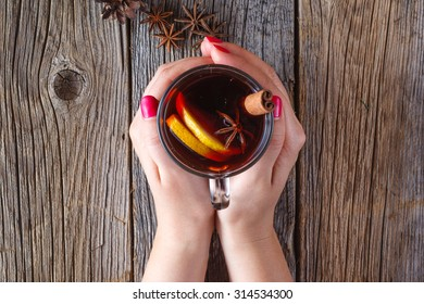 Warm mulled wine in female hands, spices on weathered wooden table. Top view