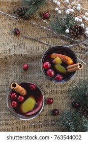Warm Mulled Wine Shot From Above With Fruit And Cinnamon Stick on Rustic Holiday Table With Pine Needles and Pine Cones