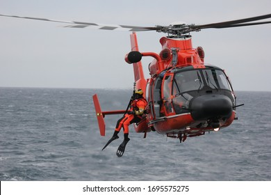 Warm orange helicopter with a survival swimmer hanging out, neutral backround.