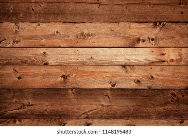 Warm orange and red brown reclaimed wood surface with aged boards lined up. Wooden planks on a wall or floor with grain and texture. Neutral stained vintage wood background.