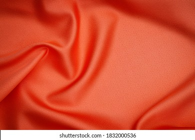 Warm orange silk cloth texture, close up. Red fabric drape background. Red orange background from draped cloth. Coral color Soft silk cloth or satin texture. - Shutterstock ID 1832000536