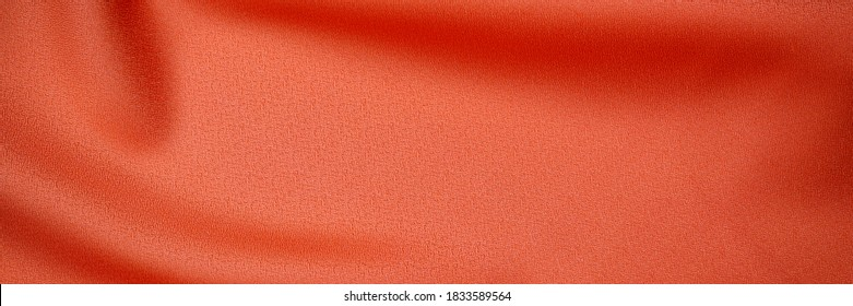 Warm orange silk cloth texture, close up. Red fabric drape background. Red orange background from draped cloth. Coral color Soft silk cloth or satin texture, banner
