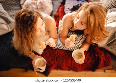 Warm photo of two young similar woman sisterhood on bed with cup of coffee, french croissant in hands, top view point