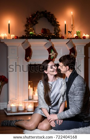 a warm picture of a married couple in love christmas like fireplace behind them