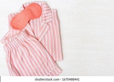 Warm pink kit for sleeping.  Soft cotton t-shirt and shorts. Comfortable clothes for healthy sleep. Pajamas are neatly complicated. copy space. Top view. Flat lay.