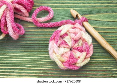 Warm pink winter yarn ball for knitting and crochet on the wooden table. Closeup photo of crochet doily. Rustic crochet thread and a bamboo hook. Rustic background for creative craft work. Work place