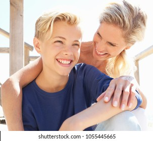 Warm portrait of mother and son sitting on wooden steps, hugging laughing joy, with fun flare light filtering through, outdoors. Family enjoying time together, loving closeness, recreation lifestyle.