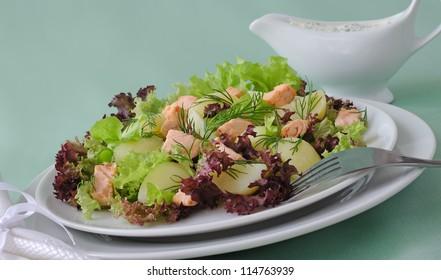 Warm potato salad with salmon salad and sour sauce