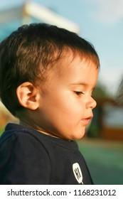 warm profile portrait of little boy with round cheeks, dark hair