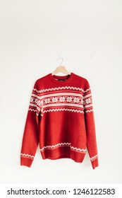 Warm red Christmas sweater on hanger on white background.