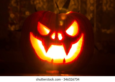 Warm red glowing Halloween pumpkin on the table with flares