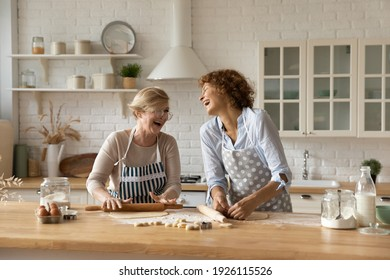 Warm relations. Happy old woman mother pensioner young female daughter grown up kid engaged in baking cookies roll dough at kitchen together laugh have fun. Elderly lady enjoy cooking with adult child - Shutterstock ID 1926115526