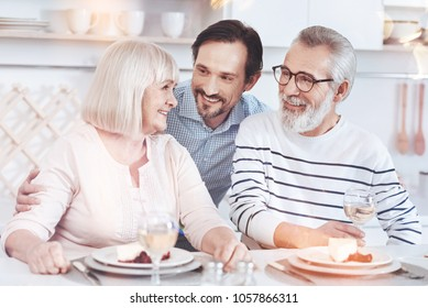 Warm relationships. Cheerful delighted aged couple sitting at the table while his adult son embracing them and resting in the kitchen