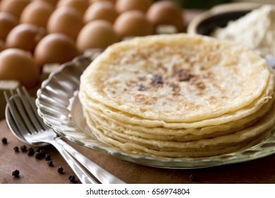 Warm Roti paratha arranged on a plate in a natural light filled kitchen.