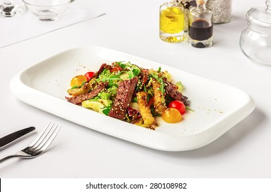 Warm salad with beef and vegetables on a rectangular white plate. served on a white table