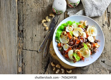 Warm salad with carrots, meat, quail eggs, cashew nuts, baked onion, top view, with spices, copy space