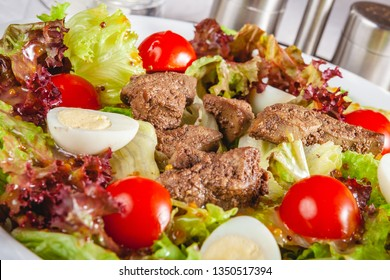 Warm salad with chicken liver, tomatoes and eggs on white plate. Close up