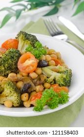 warm salad with chickpeas, broccoli, raisins on a plate, closeup