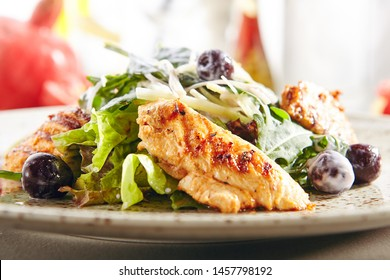 Warm salad with grilled chicken breast fillet and ripe cherries in a creamy dressing. Fresh salat with white turkey meat, green lettuce leaves, arugula and sweet berries on blurred background