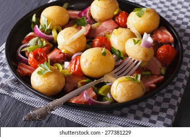 Warm salad of new potatoes with bacon and vegetables, horizontal close-up