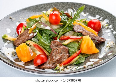 Warm salad with vegetables, arugula and veal