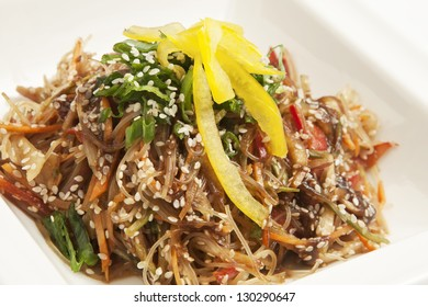 Warm salad with vegetables, rice noodles and sesame seeds