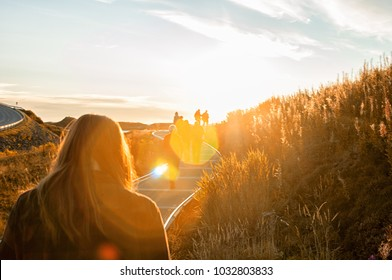 Warm shot of people walking on a grassy field with lens flares