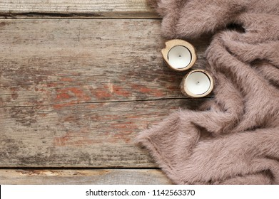 Warm soft blanket and candles on old rustic wood background. Top view point.