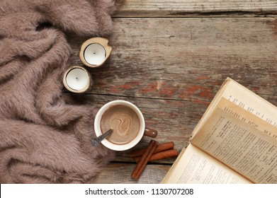 Warm soft blanket, cup of hot chocolate, candles, cinnamon sticks and open book on old rustic wood background. Cozy still life. Top view point.