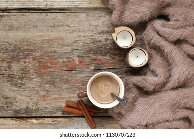 Warm soft blanket, cup of hot chocolate, candles and cinnamon sticks on old rustic wood background. Cozy still life. Top view point.