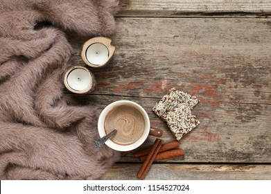 Warm soft blanket, cup of hot chocolate, candles, cinnamon sticks and crackers on old rustic wood background. Cozy still life. Top view point.