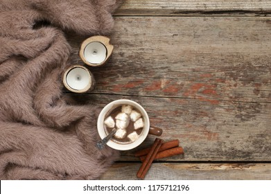 Warm soft blanket, cup of hot chocolate with marshmallow, candles and cinnamon sticks on old rustic wood background. Cozy still life. Top view point.