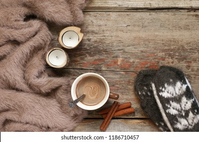 Warm soft blanket, cup of hot chocolate, candles, cinnamon sticks and woolen mittens on old rustic wood background. Winter cozy still life. Top view point.