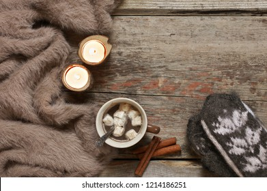 Warm soft blanket, cup of hot chocolate with marshmallow, burned candles, cinnamon sticks and woolen mittens on old rustic wood background. Winter cozy still life. Top view point.