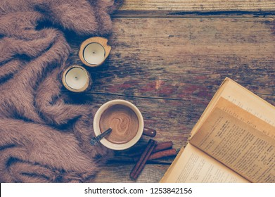Warm soft blanket, cup of hot chocolate, open book and candles on old rustic wood background. Cozy still life. Top view point.