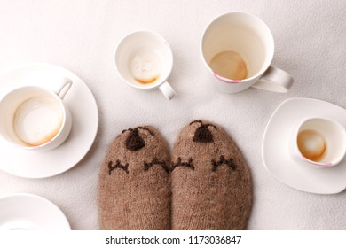 Warm soft blanket, many empty cups of espresso coffee, woolen socks. Winter fall autumn cozy still life. Lazy sleepy weekend morning concept. Top view point. Copy space