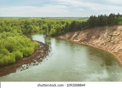 A warm spring day in the forest valley of the Russian river with a steep sandy slope. Landscape
