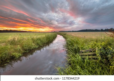 Warm summer sunrise over lowland river Grootdiep near Oosterwolde, Friesland, Netherlands