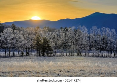 Warm sun rising over a frost covered landscape in Cades Cove of the Great Smoky Mountains