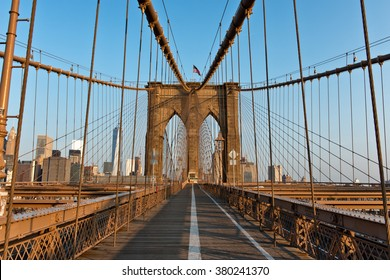 Warm Sunlight Illuminating Deserted Pedestrian Walkway on Brooklyn Bridge, Historic Landmark and Popular Tourist Destination, Connecting Brooklyn and Manhattan in New York City, New York, USA