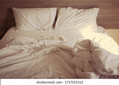 warm sunlight on Messy White Bedding Sheets And Pillow In Bedroom Background ,unmade Messy Bed After Comfort Sleep