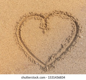 Warm sunlight shining on heart in sand- Darwing heart Symbol in sand