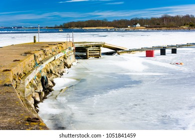 Warm and sunny spring day on the island of Hasslo, Sweden. The ice is thawing beside the pier and in the background, you can see part of Karlskrona city and a coastal home on the island.
