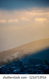 A warm sunrise breaks through dark cloud cover over the beautiful city of Cape Town, South Africa. Taken from the slopes of Table Mountain looking over Vredehoek and the lower slopes of Devil's Peak.