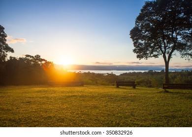Warm sunrise on green grass, Kanchanaburi, Thailand