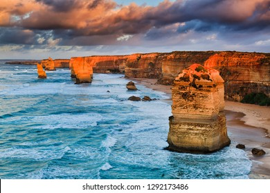 Warm sunset sunlight on limestone rocks forming twelve apostles in famous marine park of Great Ocean road in Victoria, Australia.