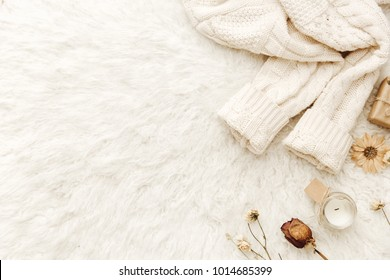 Warm sweater and dried flowers at white background. Cozy vintage. Flat lay, top view