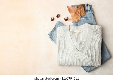 Warm sweater and jeans on neutral background. Concept autumn clothes.