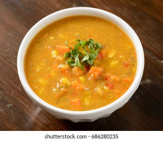 Warm sweet potato and corn soup in a white bowl on a wood background