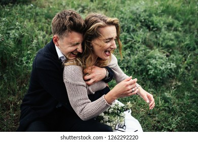Warm and tender hugs of happy couple having fun on the green lawn